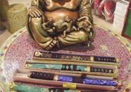 Friendly Buddha and decorative samurai swords on porcelain table. (Holwha)