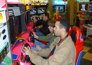 Playing a racing game in an amusement center.