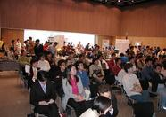 In the background, the standholders are paying attention to both the lecture and the visitors of their booths